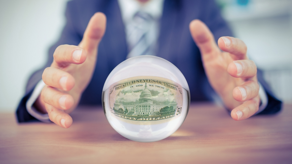 A pair of hands hovers of a crystal ball that shows a 50 dollar bill.