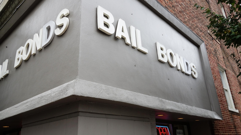 A gray and white bail bonds sign.