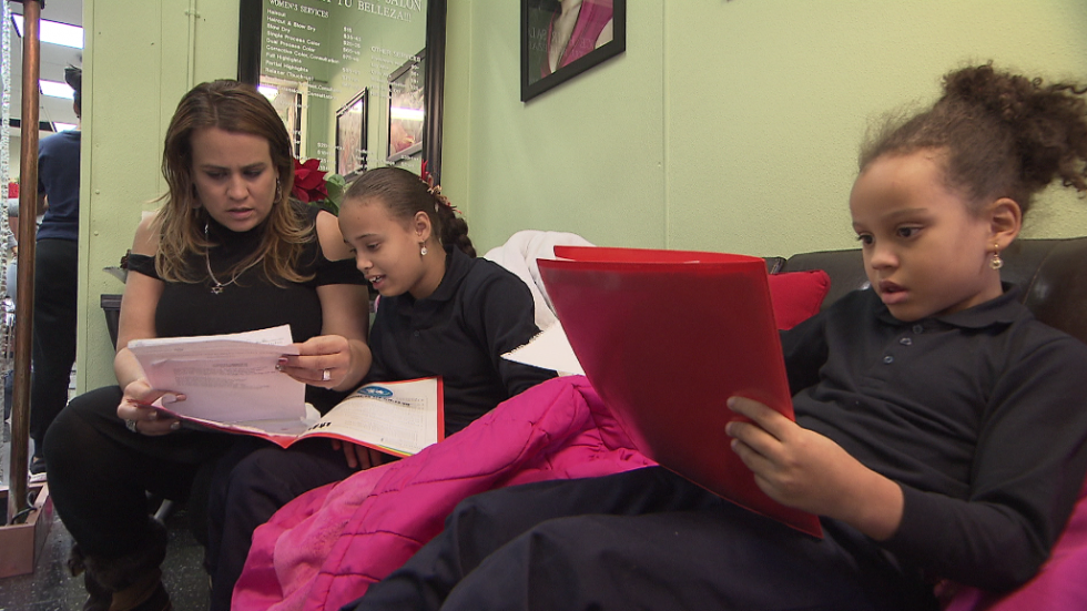 Kritzia Basmeson helps her daughters with homework after school. (Photo: ideastream)