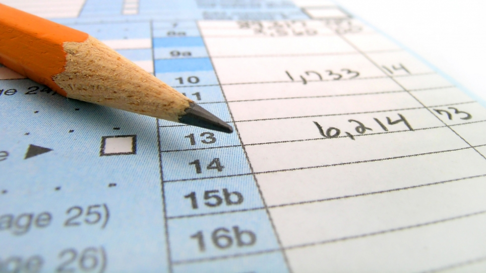 A close up shot of a pencil, resting on a tax form.