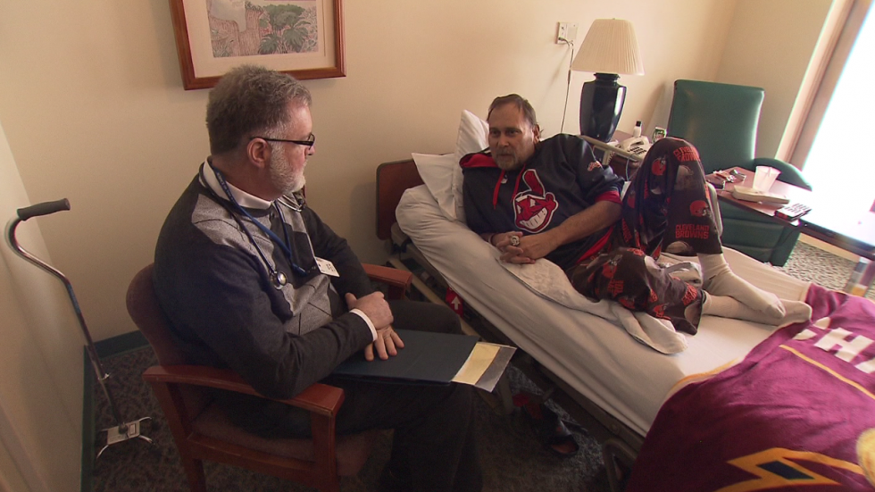 Dr. Dieter sits with a cancer patient at the hospice.