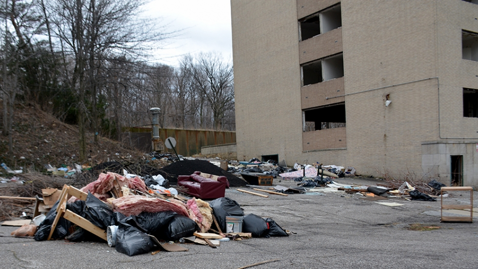Piles of refuse surround the former Huron Place Apartments.