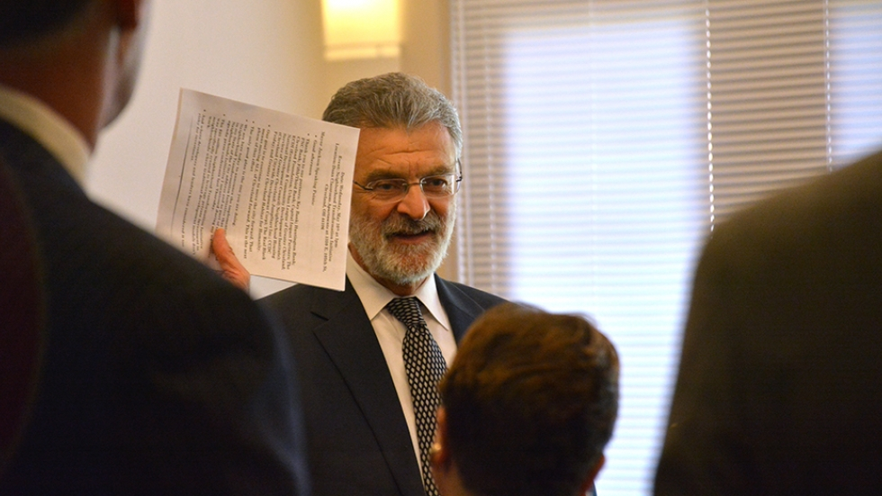 Cleveland Mayor Frank Jackson talks with bank representatives and others before a news conference Wednesday.