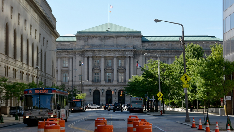 An RTA bus drives down East 6th Street with Cleveland City Hall in the background.