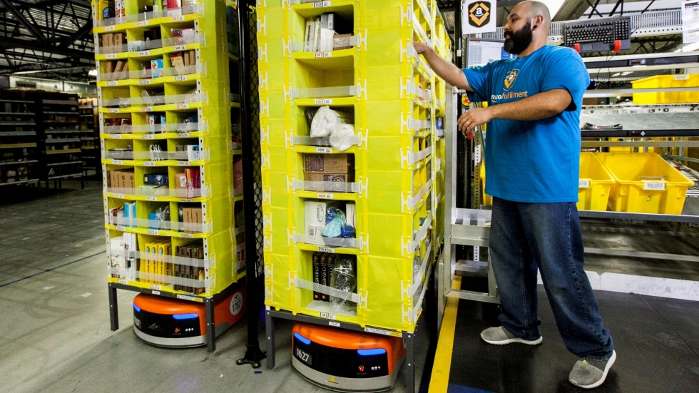"An employee at an Amazon fulfillment center, a ""picker"" as the company calls it,  next to two robots (bottom) that shuttle goods around the warehouse. [Amazon]"