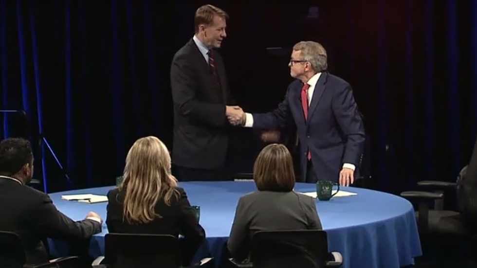 Richard Cordray and Mike DeWine stand at a blue table shaking hands.
