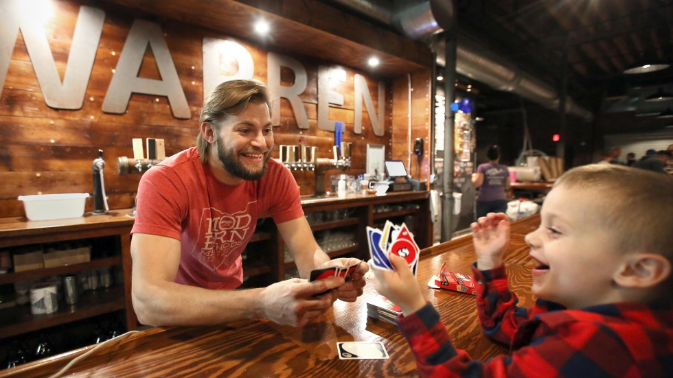Adam Keck plays with his nephew Henry at Modern Methods Brewery in Warren, Ohio