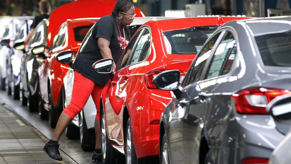 A worker at the GM plant in Lordstown, Ohio, works on a long line of Chevy Cruze vehicles.