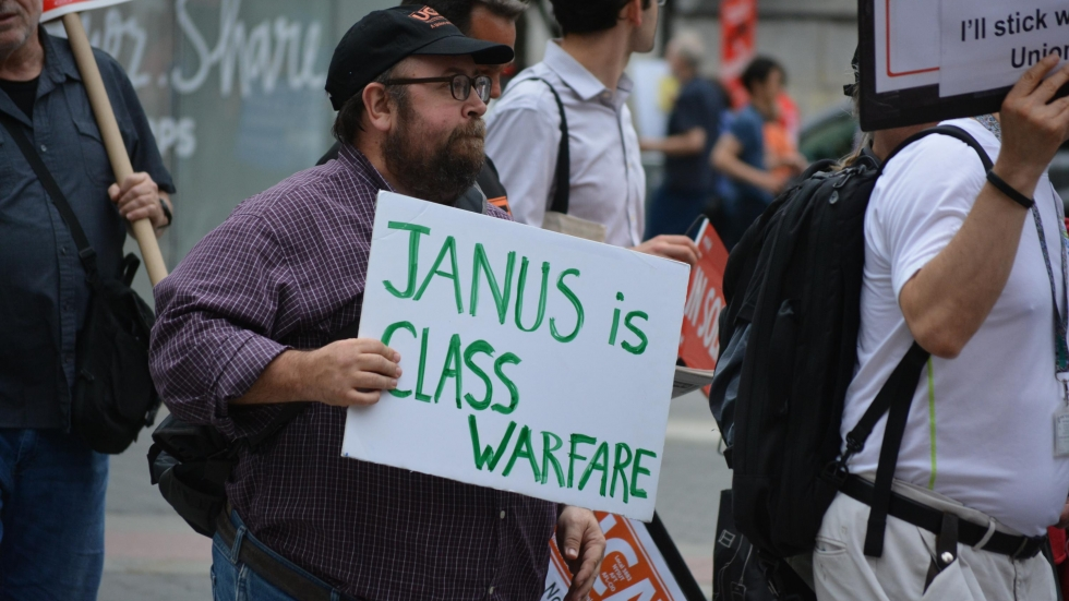 "A demonstrator in New York City holds a sign reading, ""Janus is class warfare""."