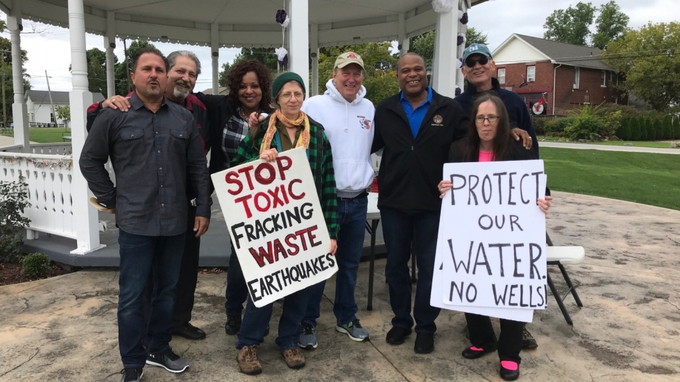 State Representative Glenn Holmes (third from right) stands with constituents holding signs against wastewater wells