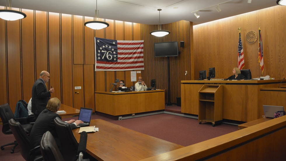 A U.S. bicentennial flag in a Cuyahoga County courtroom, where a judge conducts a hearing