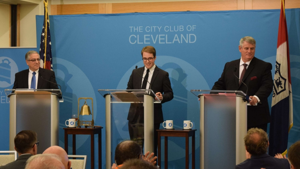 Incumbent County Executive Armond Budish, moderator Nick Castele and challenger Peter Corrigan stand at podiums during a Tuesday debate at the City Club of Cleveland