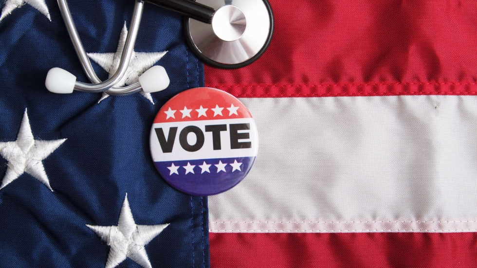 """A stethoscope and a """"vote"""" button sit on top of a US flag [Jon Schulte / shutterstock]"""