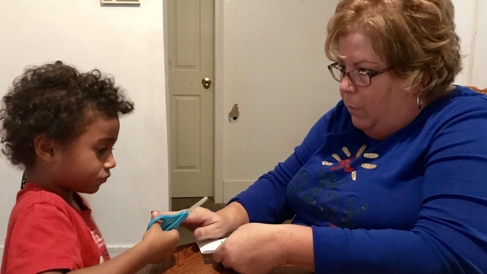 4-year-old Elijah Rowland holds a pair of scissors with SPARK parent-partner Missy Beebe
