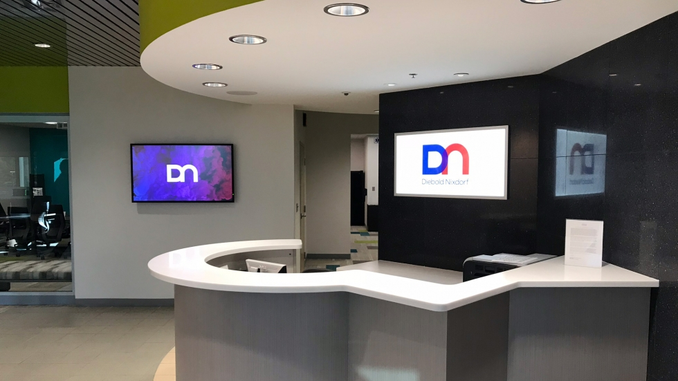 The lobby of Diebold Nixdorf's U.S. headquarters in North Canton, Ohio. A white counter has two flat screen TVs behind it that display the company logo. [Adrian Ma / ideastream]