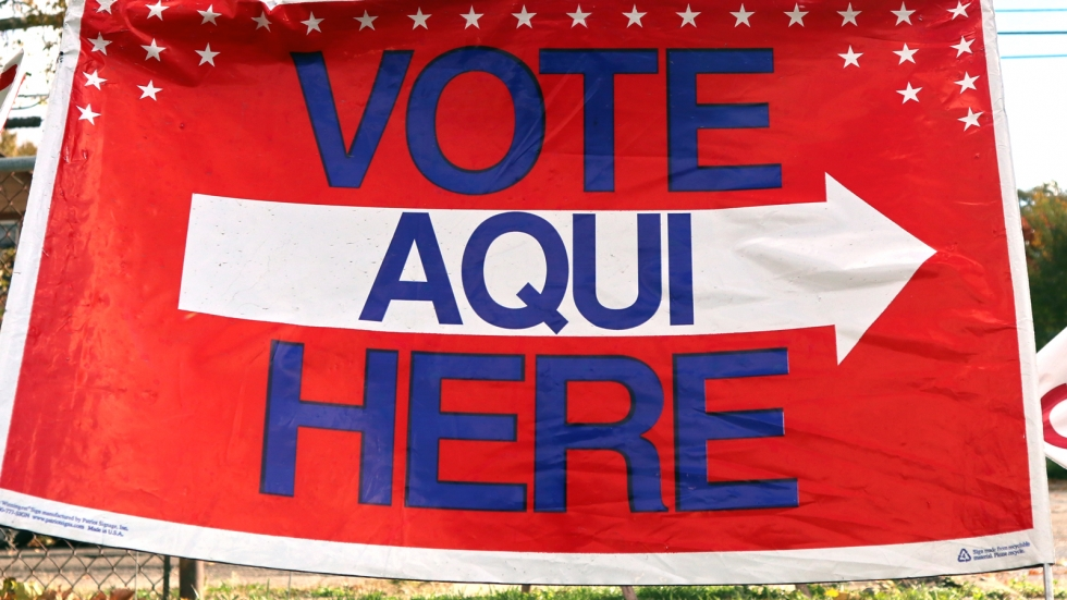 """A sign that says """"Vote Aqui Here"""" in red, white, and blue."""