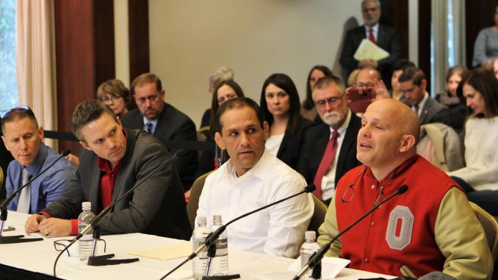 Accusers of a former Ohio State doctor sit at a table addressing university trustees.
