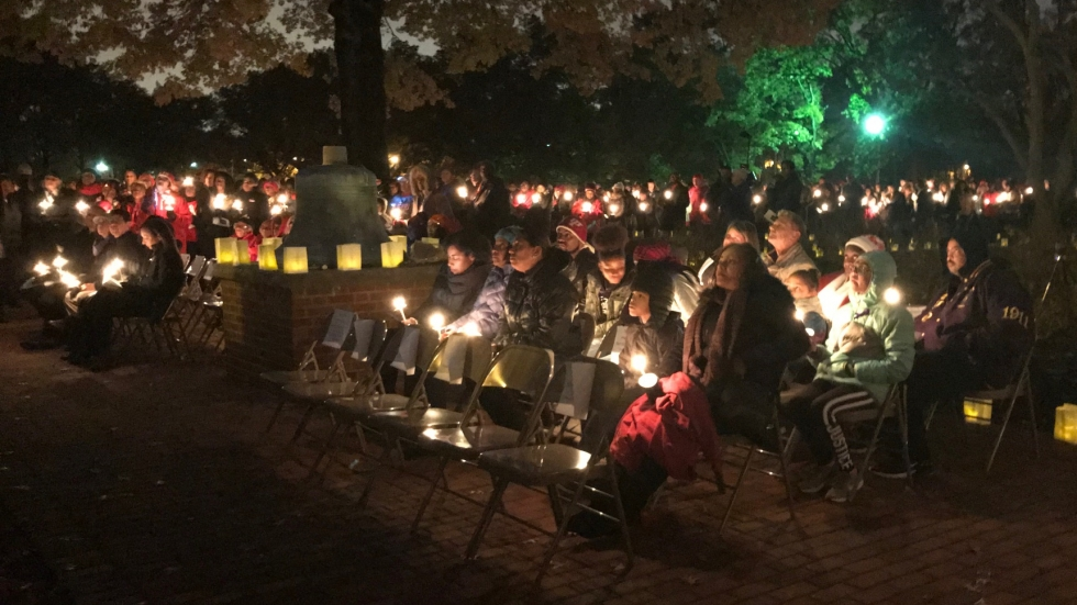People seated with candles at a vigil for Shaker Heights teacher Aisha Fraser.
