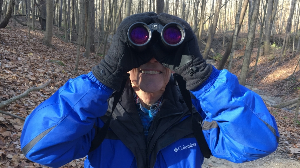 Akron-area birder Mike Edgerton holds binoculars to his eyes looking for winter birds.