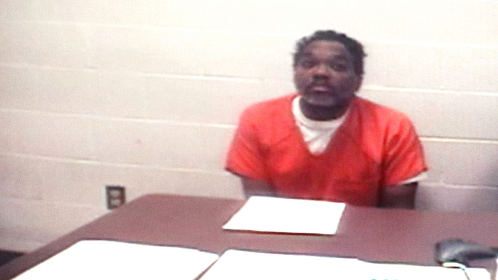 A grainy-looking video feed showing Lance Mason, in an orange shirt sits, sitting at a brown table in a room with white walls. His hands are under the table.