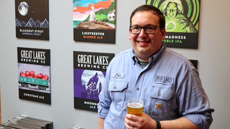 A man with glasses, and wearing a blue shirt, is holding a beer. He's smiling, standing in front of a wall of posters depicting several of Great Lakes Brewery's beer labels.