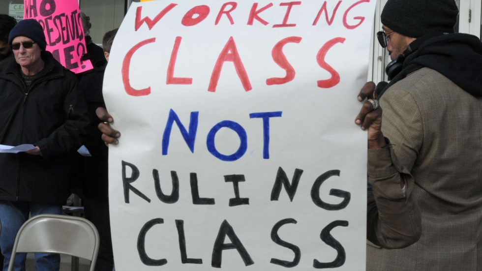 "Activists demonstrating outside an economic planning meeting hold a sign reading, ""Working class not ruling class""."