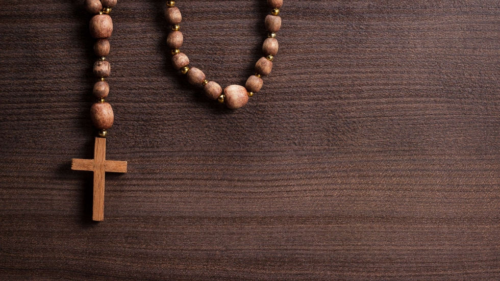 Wooden cross and beads on a brown table.