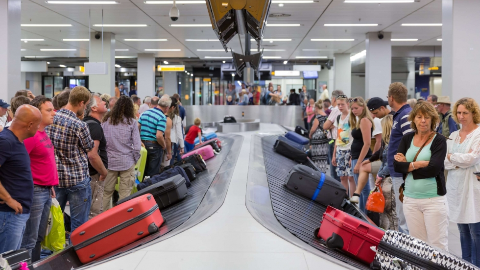 Travelers watch for their luggage at an airport baggage carousel.