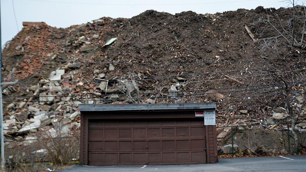 A mound of dirt and debris rises behind a garage in East Cleveland