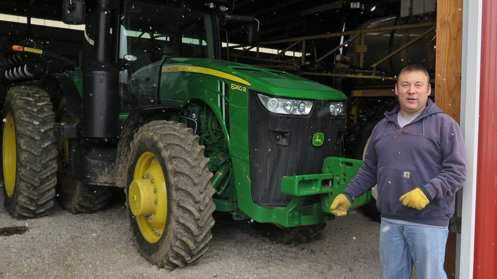 Tom Trout of Hickory Tree Farms in Medina County stands beside his tractor.
