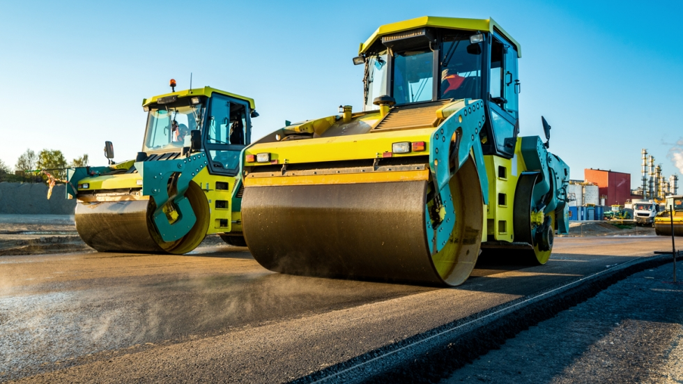 Two green and blue steamrollers rolling over wet pavement.
