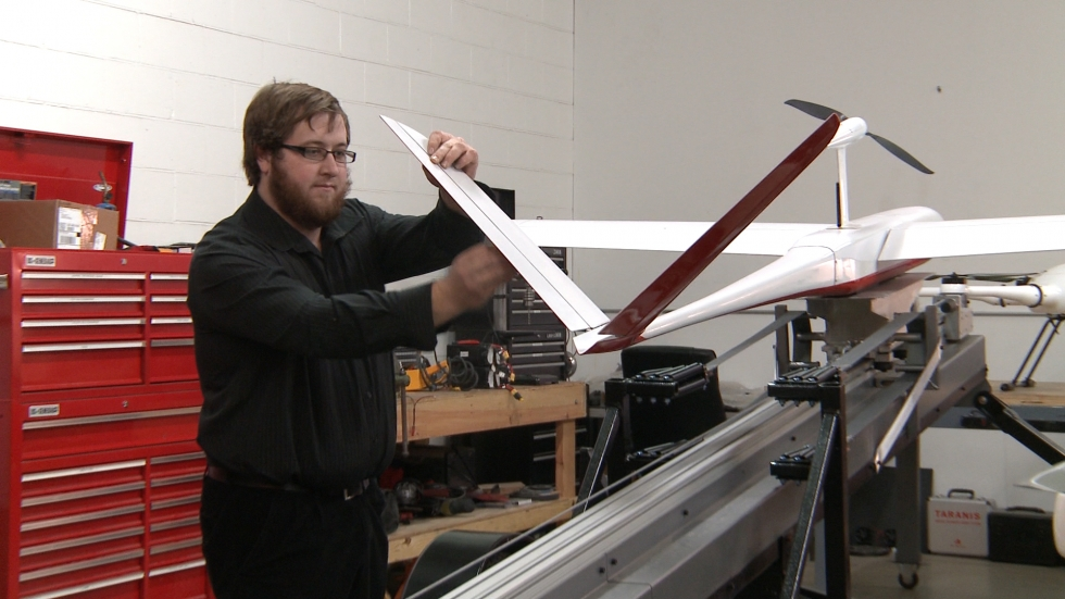 An employee of Unmanned Solutions Technology in Dayton inspects the wing of a drone built for Sinclair Community College. (Ashton Marra/ideastream)