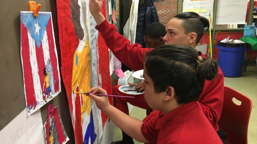 Isaiah Butchart and his classmates practice painting the mural they'll paint in a Puerto Rican elementary school when they travel to the island to volunteer over their spring break. (Ashton Marra/ideastream)