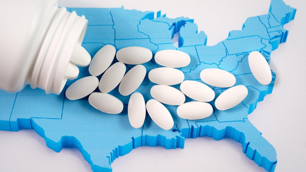 A bottle spills pills across a map of the United States.