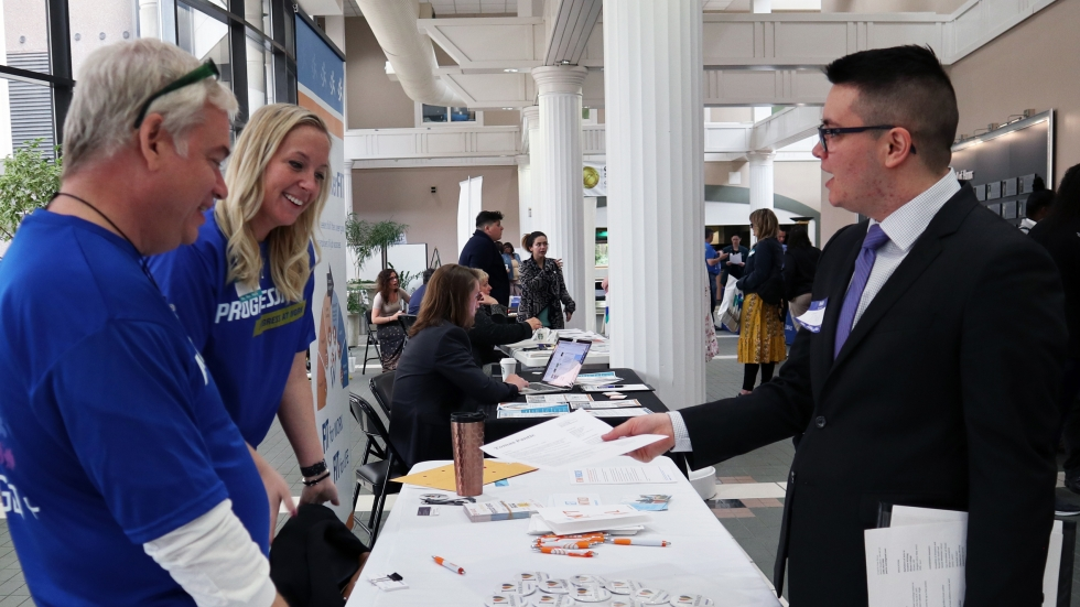 """A jobseeker speaks with recruiters at career fair hosted by MetroHealth in Cleveland. Although the event was open to the public, it was advertised as a """"Transgender Job Fair."""" [Adrian Ma / ideastream]"""