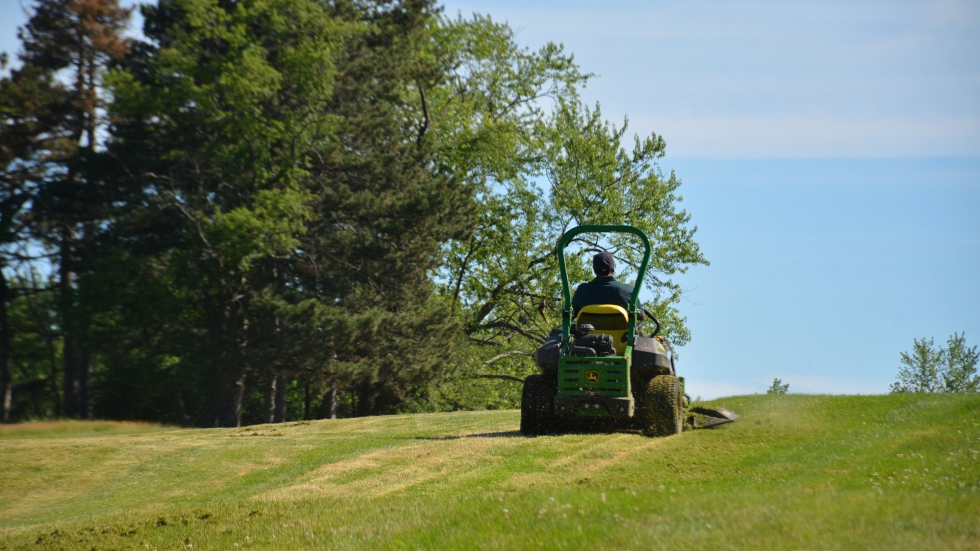 A man drives a riding lawnmower over a fairway at Highland Park Golf Course