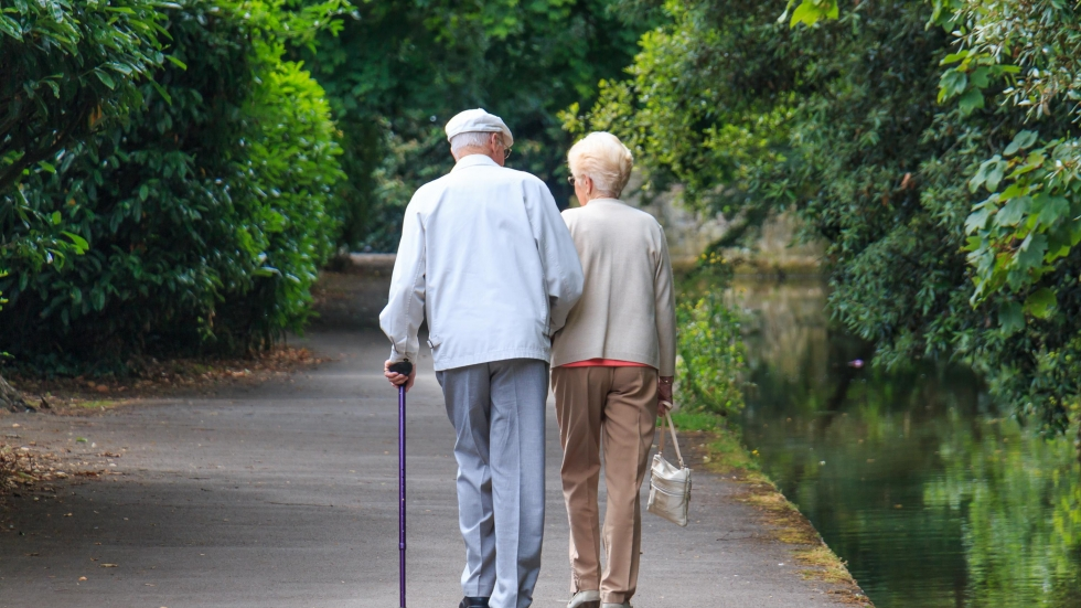 An elderly couple, the man walking with a cane, enjoys a stroll through a park. {Shutterstock]