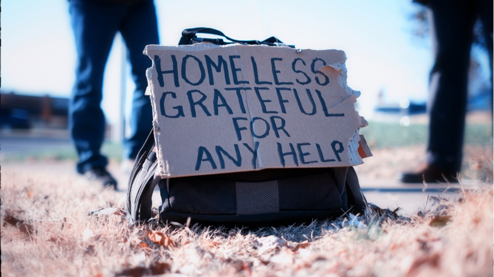 "A sign on a backpack reads, ""Homeless, grateful for any help."""