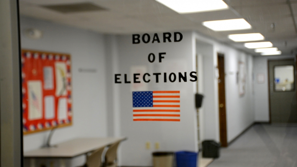 A glass door leading to the Portage County Board of Elections, with an American flag decal on the window