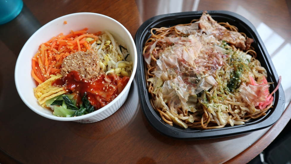 Two bowls of food purchased at a Lawson in Tokyo's Hiroo neighborhood. The one on the left contains several vegetables, including carrots, bok choy, and bean sprouts, arranged in a circle on top of rice. The other dish contains brown-colored noodles topped with flakes of dried bonito.