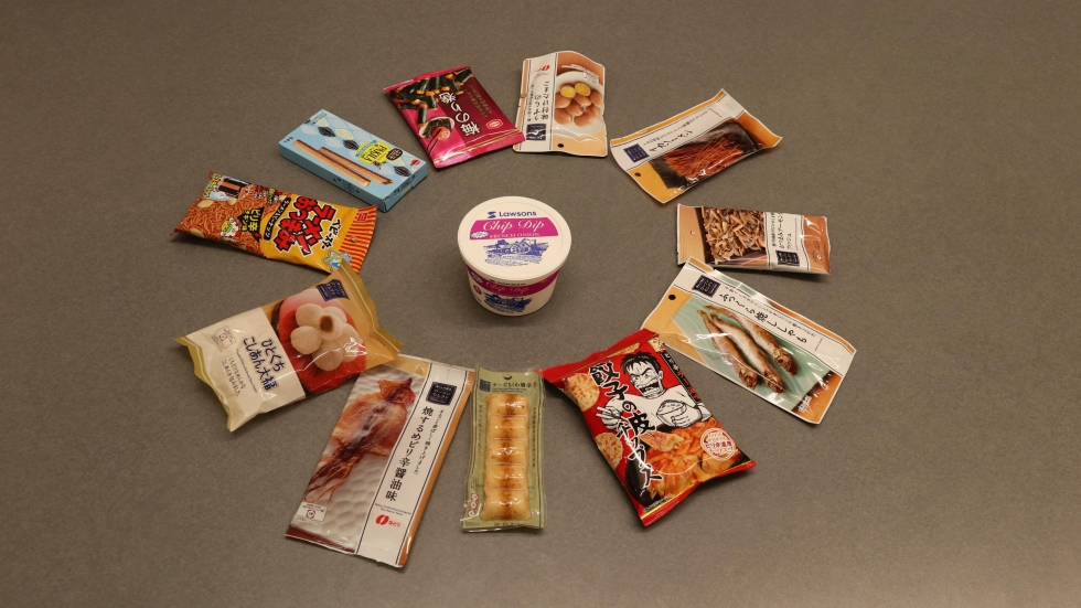 A plastic container of Lawson's brand chip dip, with various packaged snacks from Lawson in Japan appearing in a circle around it.