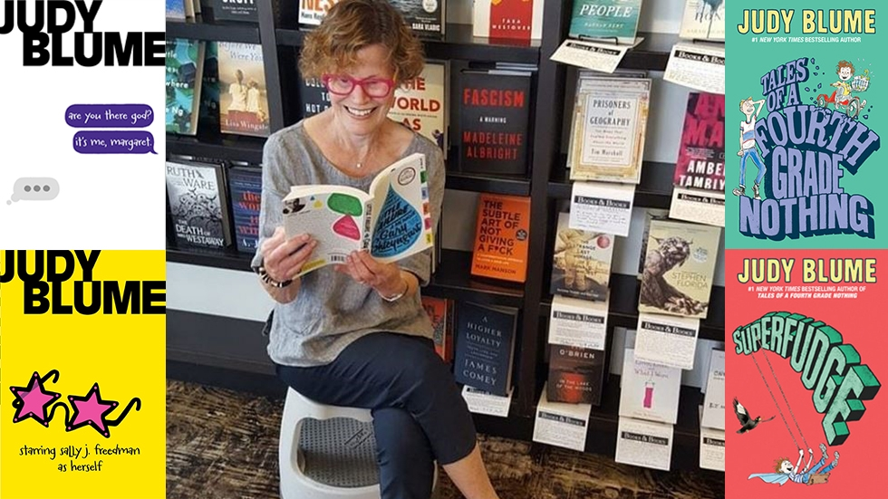 Judy Blume sits amongst books flanked by covers of her most famous titles.