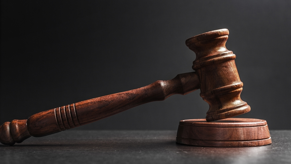 A wooden judge's gavel lays on a table against a dark background.