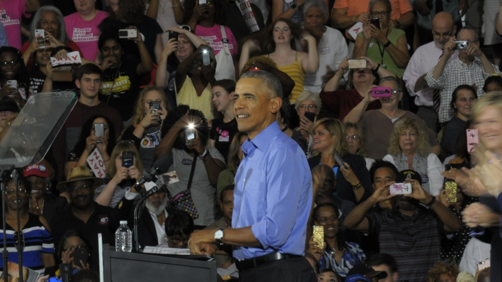Barack Obama stands at a podium in front of a gym full of supporters