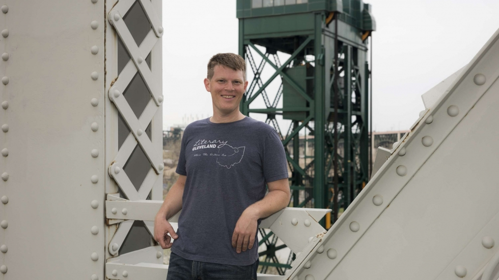 Lee Chilcote stands on a bridge in Cleveland in front of industrial buildings in the Flats.