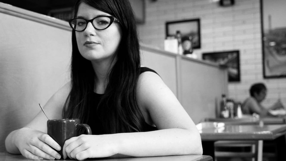 Nikki Delamotte sits at a table in a restaurant. The black and white photo was her Twitter profile picture. [Jacqueline Bon]