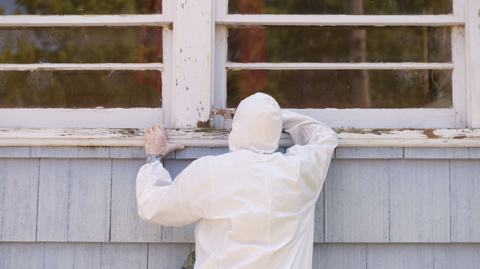 Stock photo of a worker in a white uniform scrapes paint from an old building.