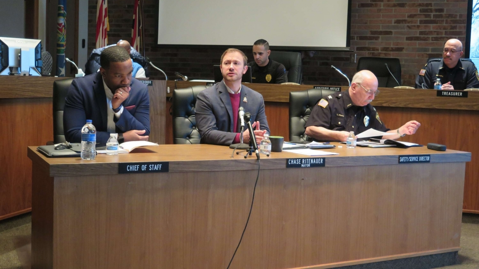 Lorain City Schools CEO David Hardy, Jr, Lorain Mayor Chase Ritenauer, and Lorain Police Chief Cel Rivera sit at a table in city council chambers for the 19th annual Speak Up and Speak Out event. [Annie Wu / ideastream]