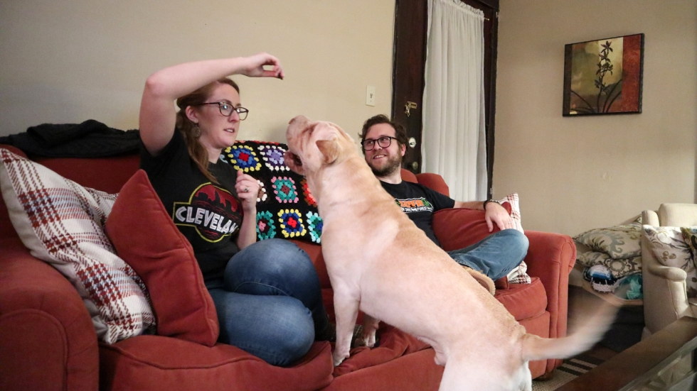 A woman and man, both in their early 30s, sit on a red couch with their dog. The woman is holding a dog treat in one hand above her head, and the dog is lunging for it, it's tail is wagging.