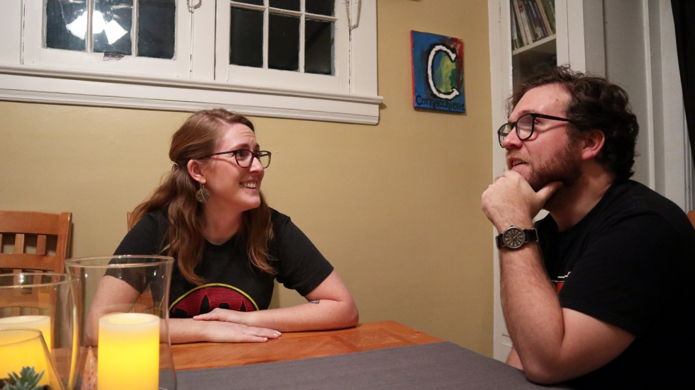 A man and woman, both in their 30s sit at a wooden table. They are chatting. The woman is smiling. The man has his hand on his chin.